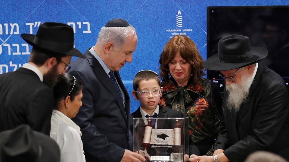 Moshe Holtzberg, who survived during the 2008 Mumbai attacks, presents a souvenir to Israeli Prime Minister Benjamin Netanyahu at Chabad House in Mumbai on  January 18.