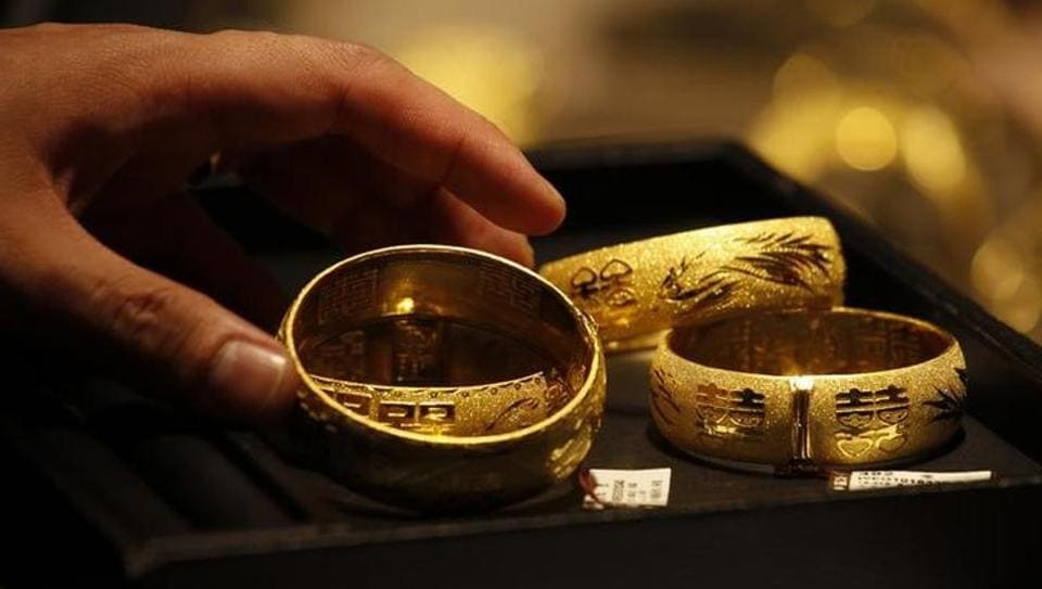 A shop attendant shows two pairs of 24K gold bracelets to a customer inside a jewellery store.