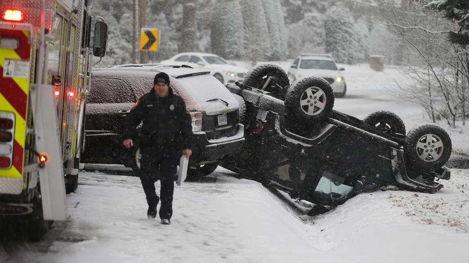 A police officer walks from the scene of an overturned Jeep after an accident on a snow-covered road in Richmond, Va., Wednesday, Jan. 17, 2018. A winter storm is making it's way through Virginia.