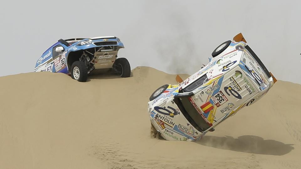 The Mitsubishi rally car driven by Cristina Gutierrez Herrero and Gabriel Moiset Ferrer, both of Spain, flips over between Lima and Pisco. (Ricardo Mazalan / AP)