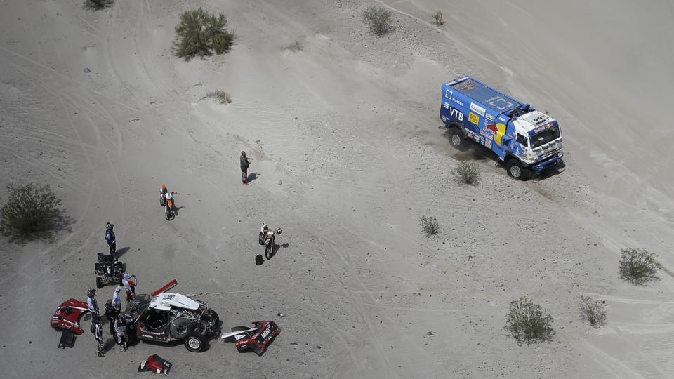 Russians Eduard Nikolaev and Evgeny Yakovlev, race their Kamaz as Mikko Hirvonen, of Finland, and co-driver Andreas Schulz, of Germany, work on their Mini during Stage 11 between Belen and Chilecito/Fiambala, Argentina. (Ricardo Mazalan / AP)