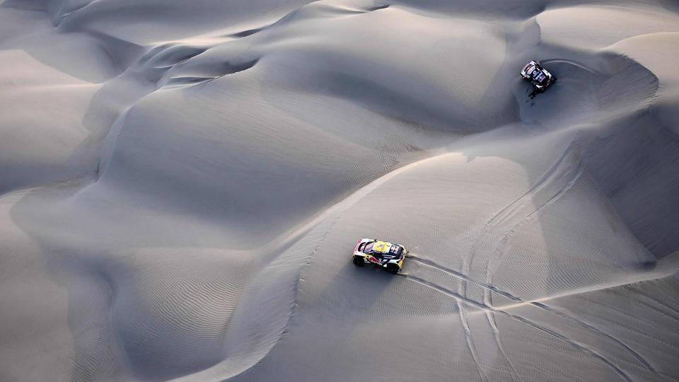 Peugeot's Stephane Peterhansel and Jean Paul Cottret seen bottom as the team's Spanish drivers Carlos Sainz and Lucas Cruz are stuck in the dunes of Tanaca during between San Juan De Marcona and Arequipa. The fifth stage was won by defending champion Peterhansel. (Franck Fife / AFP)