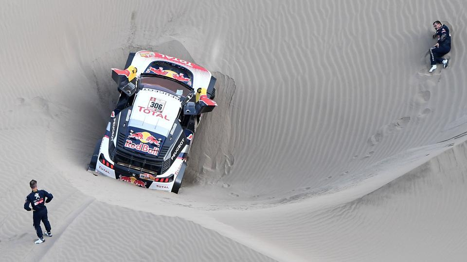 Peugeot's Daniel Elena (R), from Monaco, gestures on the ground after getting injured when he and French driver Sebastien Loeb ran into sand during Stage 5. Loeb was forced to pull out of the rally after the accident. (Franck Fife / AFP)