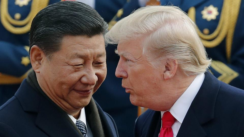 US President Donald Trump, right, chats with Chinese President Xi Jinping during a welcome ceremony at the Great Hall of the People in Beijing on November 9, 2017.