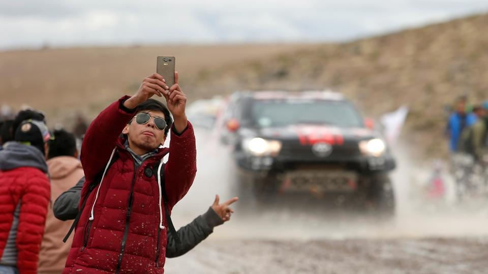 A fan takes a selfie as cars pass by during Stage 6 from Arequipa to La Paz, Bolivia . (Andres Stapff / REUTERS)