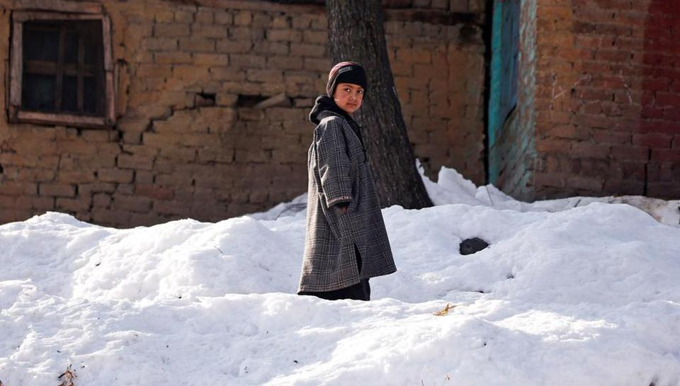 A boy stands on snow outside his home on a cold winter morning at Haripora village in south Kashmir.