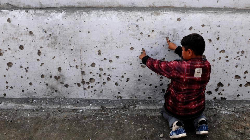 A boy shows splinters marks of mortar shell on a wall fired from the Pakistan side, in Arnia district of Jammu and Kashmir, on Thursday.
