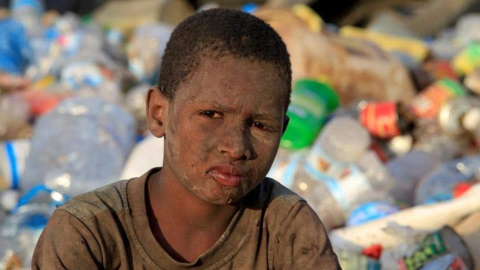 "Ayoub Mohammed Ruzaiq, seen caked in dirt and grime from sifting through mounds of garbage. ""We eat and drink the food that is thrown away,"" described the 11-year-old. ""We collect fish, meat, potatoes, onions and flour to make our own food."" (Abduljabbar Zeyad / REUTERS)"