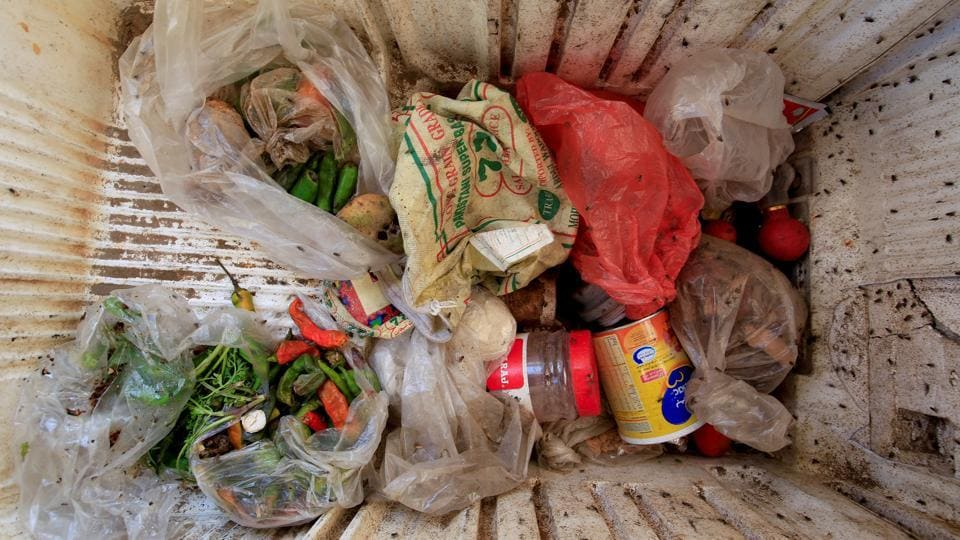 Odd bits and pieces of scavenged vegetables, tinned food and other ingredients are stored in a broken refrigerator, swarmed by flies,  for future use by the 18-member Ruzaiq family. (Abduljabbar Zeyad / REUTERS)