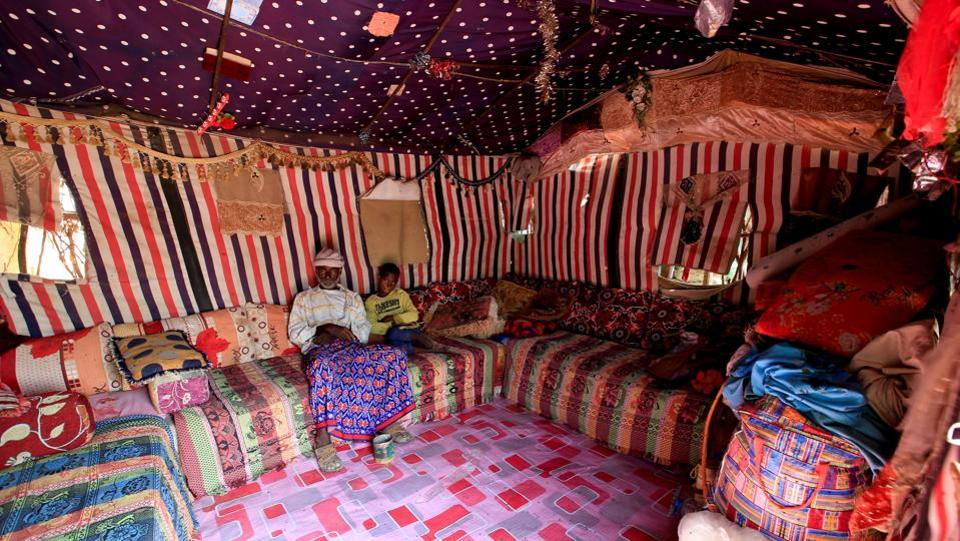 The family patriarch Mohammed Ruzaiq (L), 67, and his son Ayoub  sit in the tent they share with other members of the family.