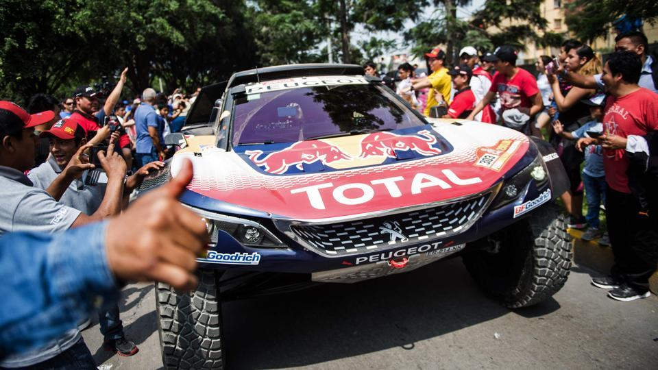 Fans show their support as Peugeot's Carlos Sainz and co-driver Lucas Cruz pass by, on the first day of the 2018 Dakar Rally, ahead of the Lima-Pisco Stage 1. (Ernesto Benavides / AFP)