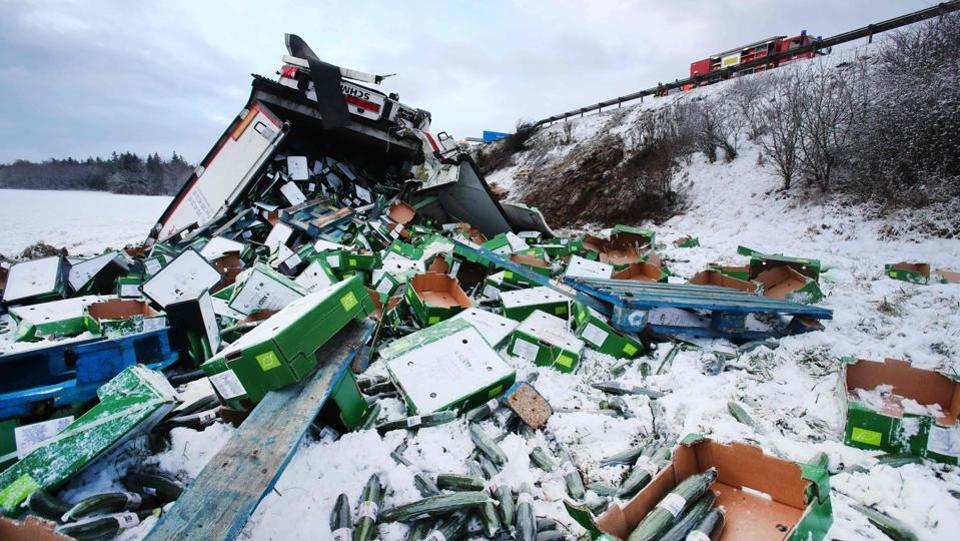 Crates of cucumbers lie scattered in the snow after a cargo truck slid off a snow-packed highway in Germany on January 17. (Bodo Schackow / AFP)