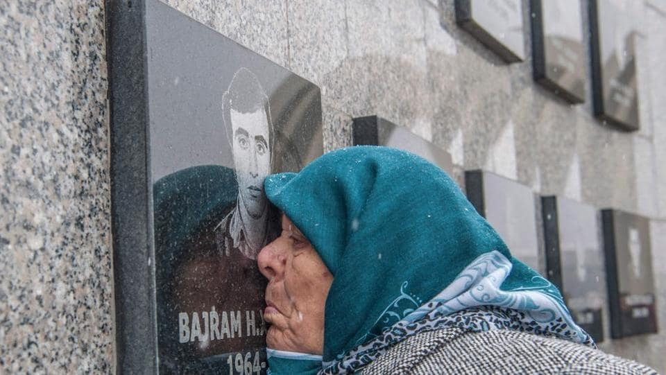 A Kosovo-Albanian woman Vezire Gjeladini, 76, kisses the picture of her son etched into a commemorative plaque on a wall dedicated to victims of the Racak massacre on January 15. In 1999, forty-five Albanian civilians were killed by Serb forces in the village of Racak. (Armend Nimani / AFP)