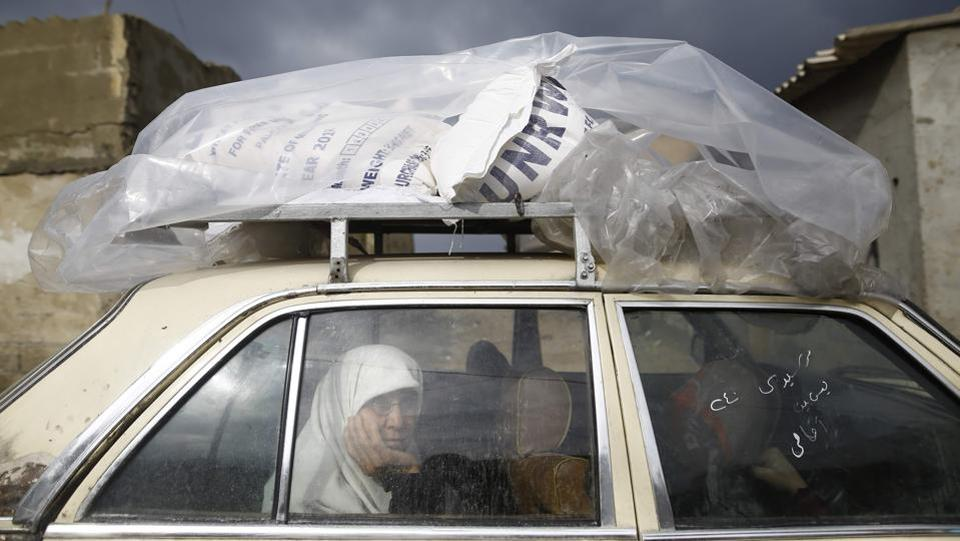 A Palestinian woman rides in a car after collecting aid provided by the UN agency for Palestinian refugees in Gaza City on January 17. (Mohammed Abed / AFP)