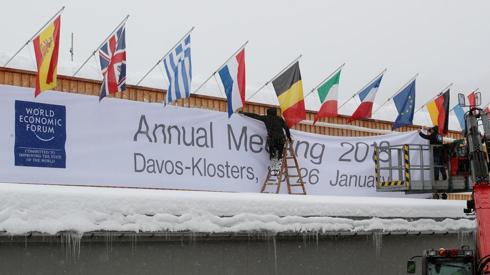Workers fix a banner on the frontage of the congress centre, the venue of the upcoming World Economic Forum (WEF) in the Swiss mountain resort of Davos, Switzerland on January 18.