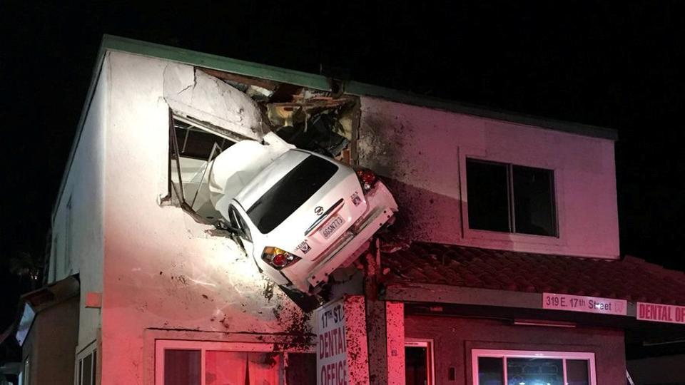 A car dangles off the second floor of a building after speeding into a median and going airborne, according to local media, in Santa Ana, California on January 14. (REUTERS)