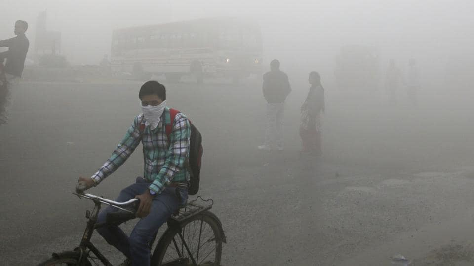Commuters wait for transport amid a thick blanket of smog on the outskirts of New Delhi.