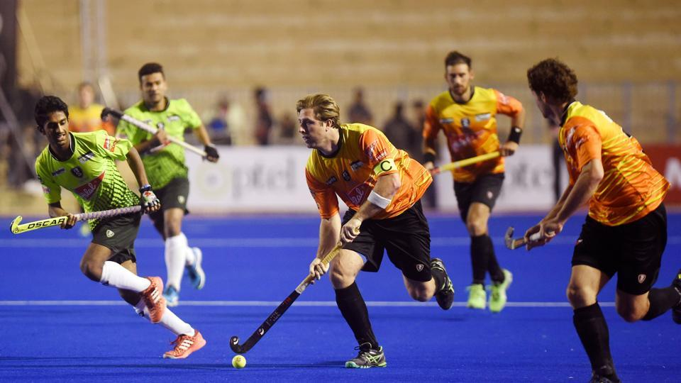 World XI field hockey captain Roderick Weusthof (C) vies with Pakistani players (L) during their first match at the Abdul Sattar Edhi hockey stadium in Karachi.