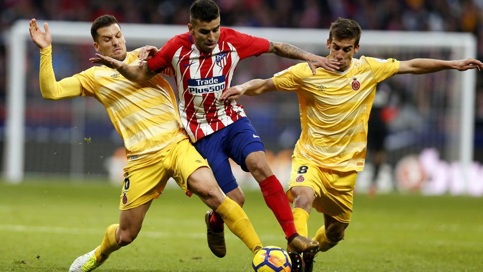 Atletico Madrid's Angel Correa, centre, tussles for the ball with Girona's Alex Granell, left, during a La Liga.