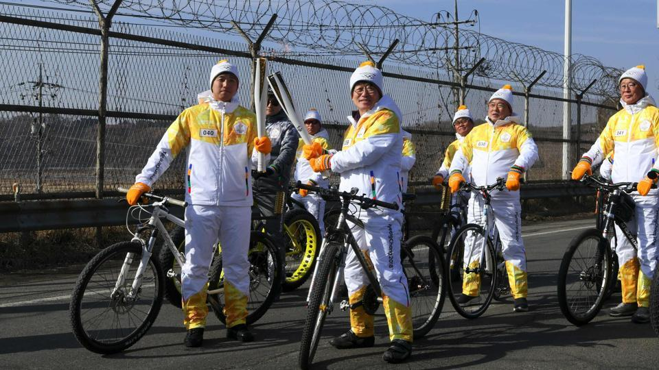 Torchbearers 'kiss' with their torches to pass the Olympic flame in front of a military fence on the road leading to the border truce village of Panmunjom during the PyeongChang 2018 Torch Relay in Paju on January 19, 2018.