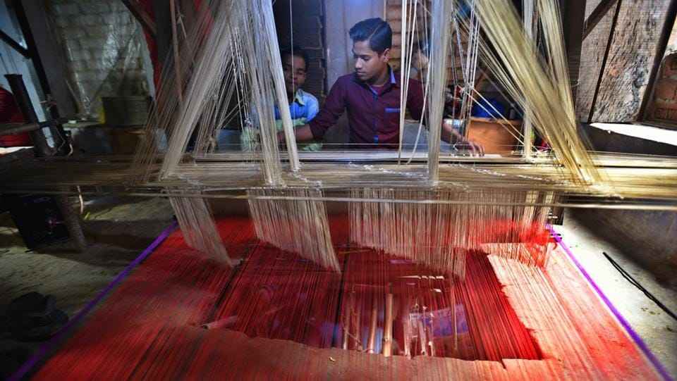 "Barkhat, a weaver works with a handloom, the traditional tool for making Banarasi silk fabric. In localities where the clacking of handlooms once signalled the craft, the powerloom's buzz has grown increasingly louder. 72-year-old Maqbool Hasan, a master weaver, remembers a time when his family owned 500 handlooms. ""Now we have only 200 looms. No one wants to weave on a handloom anymore,"" he said. (Raj K Raj / HT Photo)"