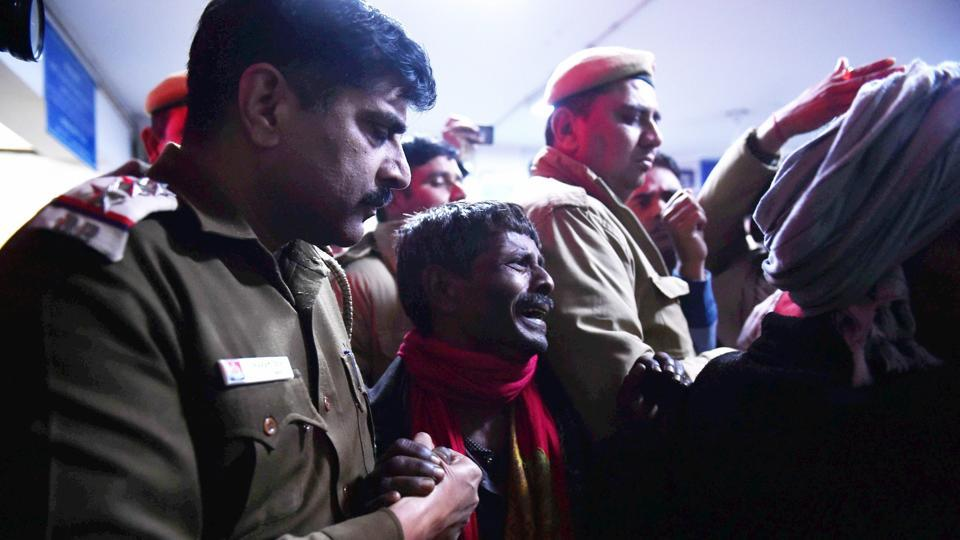 Policemen comfort a relative mourning the death of victim at a hospital after a two-storey cracker factory caught fire in north Delhi's Bawana industrial area on Saturday.