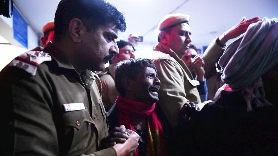 Policemen comfort a man mourning the death of a relative at a hospital after a two-storey cracker factory caught fire in north Delhi's Bawana.  (PTI)