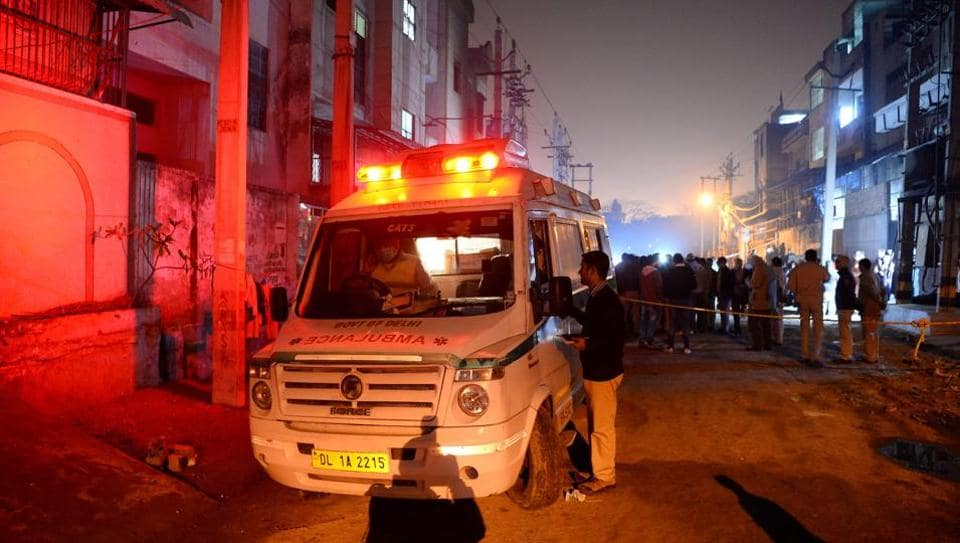 An ambulance is parked in front of a plastic factory in the Bawana industrial area on the northern edge of New Delhi on January 20, 2018 after a fire killed at least 17 workers.