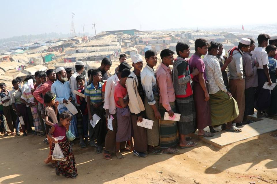 Rohingya refugees stand in a queue to collect aid supplies in Kutupalong refugee camp in Cox's Bazar, Bangladesh.