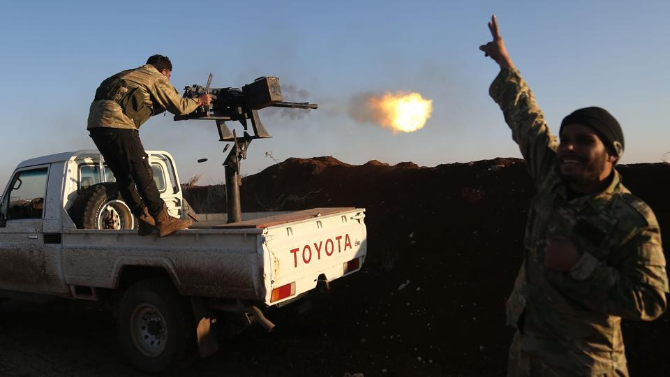Turkish-backed fighters from the Free Syrian Army stand in the Tal Malid area, north of Aleppo, as they fire towards Kurdish People's Protection Units positions in Afrin, on Saturday.