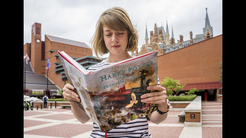 A reader engrossed in the illustrated version of J.K. Rowling's 'Harry Potter and the Philosopher's Stone' by Jim Kay outside the British Library, London.  (Tony Antoniou)