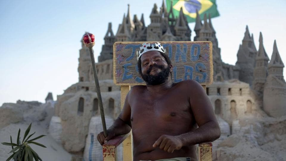 "They say a man's home is his castle and Marcio Matolias has lived in his - albeit made of sand - on a beach in Rio de Janeiro for the past 22 years. In Barra da Tijuca, a wealthy beachside neighbourhood, neighbours and friends call him ""The King"". He gladly assumes the role and poses willingly for passers-by, sceptre in hand, on his throne outside his meticulously-sculpted home. (Mauro Pimentel / AFP)"