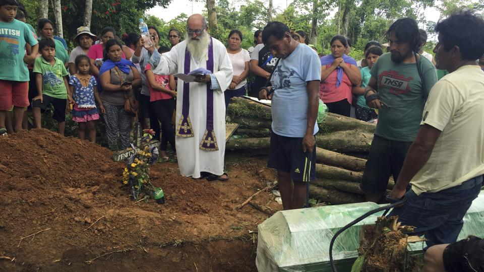 Below a canopy of trees in the Peruvian Amazon, drunken miners carry in the casket of a man whose search for gold ended with a bullet in his stomach. 70-year-old Spanish Reverend Pablo Zabala presides over the funeral, singing as the coffin is lowered into the dirt in a cemetery where the graves of about 50 other illegal miners are marked with plain black crosses. (Franklin Briceno / AP)