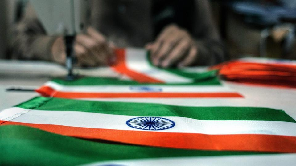 A tailors stitches together a national flag at his workshop ahead of Republic Day, in New Delhi.