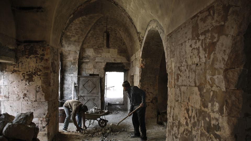 Syrian men remove rubble from a damaged shop at the old market in the old city of Aleppo, Syria. Fighting has long died down in Syria's largest city but Aleppo's centuries-old market still has to come back to life, more than a year after government forces retook rebel-held neighborhoods around the Old City.