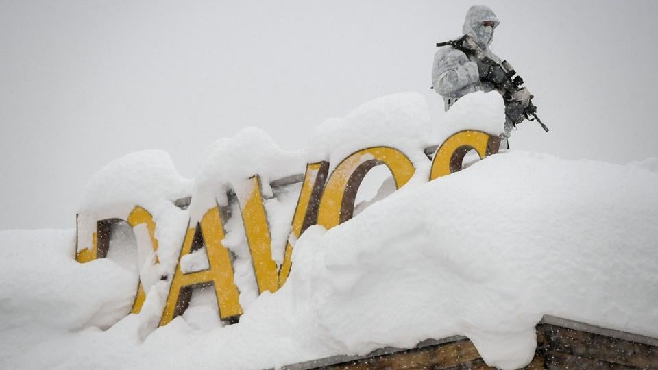 An armed security personnel wearing camouflage clothing stands on the rooftop of a hotel, next to letters covered in snow reading