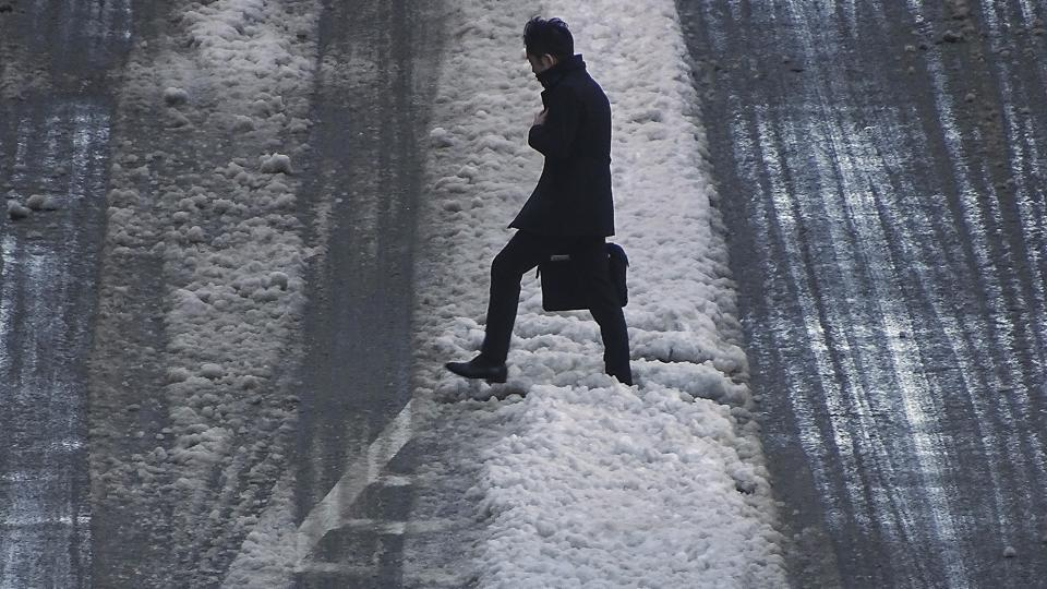 A man walks on snow-covered street Tuesday Jan. 23, 2018 in Tokyo.