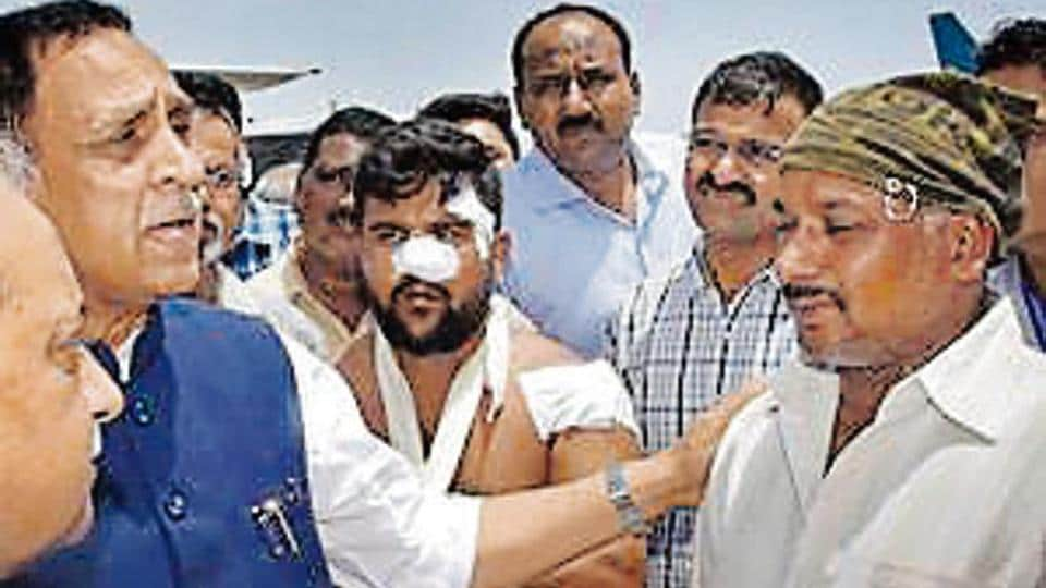 Gujarat chief minister Vijay Rupani interacts with Sheikh Saleem Gafur, the driver of the bus, after the attack. (PTI file photo)