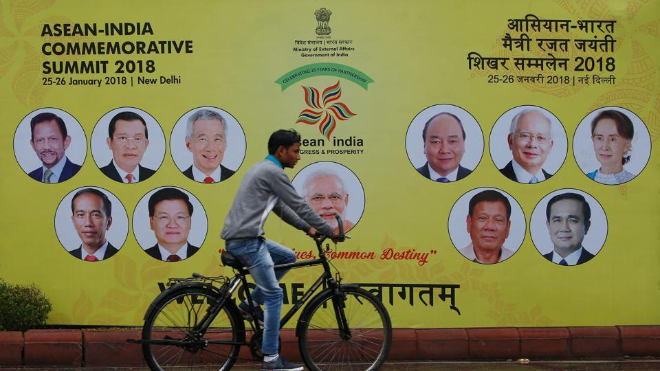 A cyclist rides past an Asean-India Commemorative Summit billboard, New Delhi, India, January 23, 2018