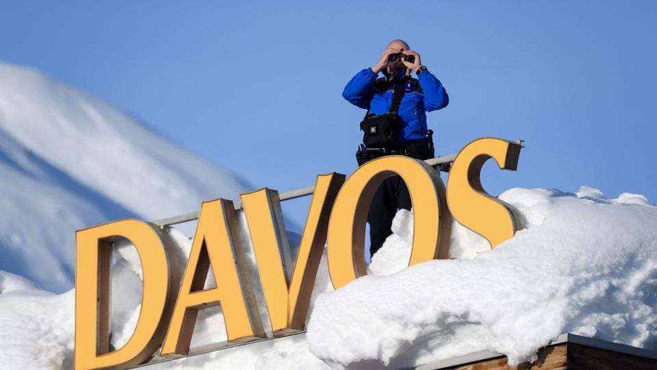 Swiss armed security personnel stand guard on the rooftop of a hotel, next to letters covered in snow reading