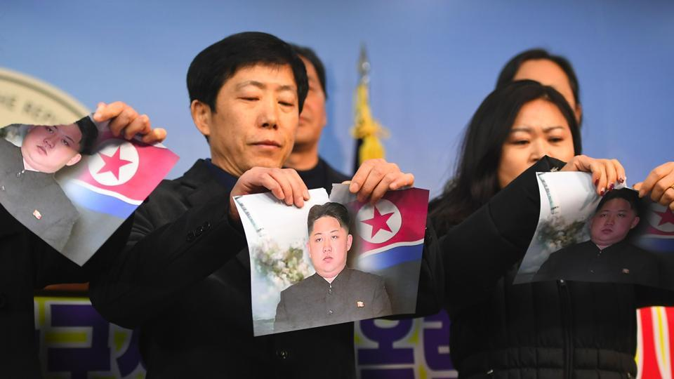 North Koreans who defected to the South tear pictures of North Korean leader Kim Jong-Un during a press conference against the North's attendance at the Pyeongchang Olympics, at the National Assembly in Seoul on January 24, 2018.