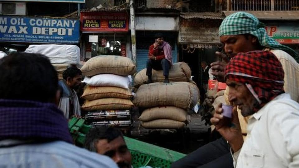 A labourer talks on his mobile phone as he sits on the sacks of spices at a wholesale spice and chemical market in Delhi.