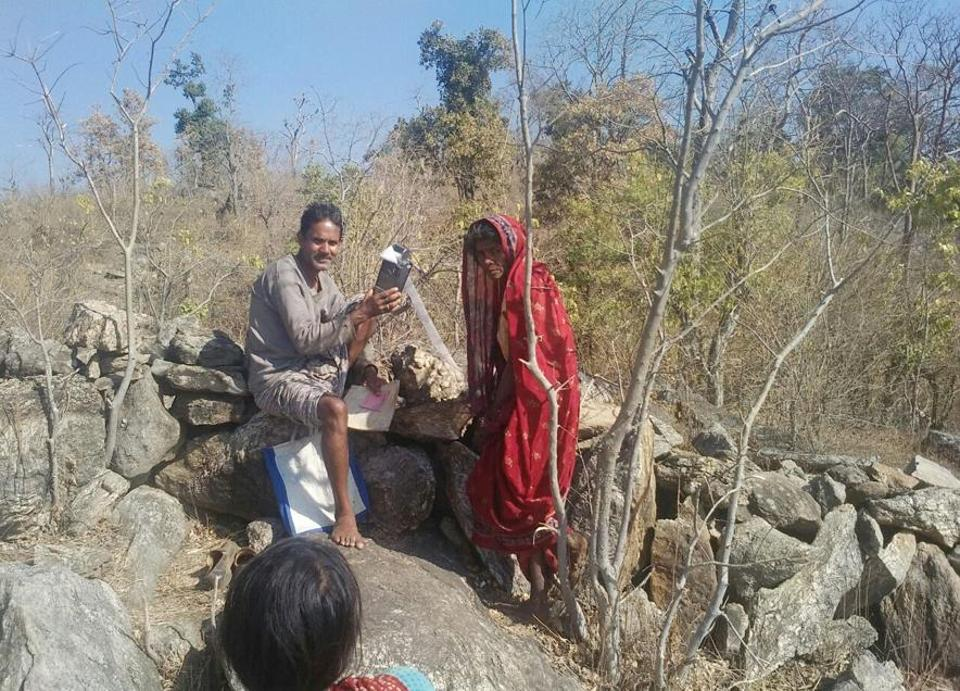 A public distribution system (PDS) dealer with a POS (point of sale) machine and a PDSbeneficiary atop a hill due to poor internet connectivity at Rewat Khurd village in Latehar district of Jharkhand. (Vishal Sharma / HTPhoto)