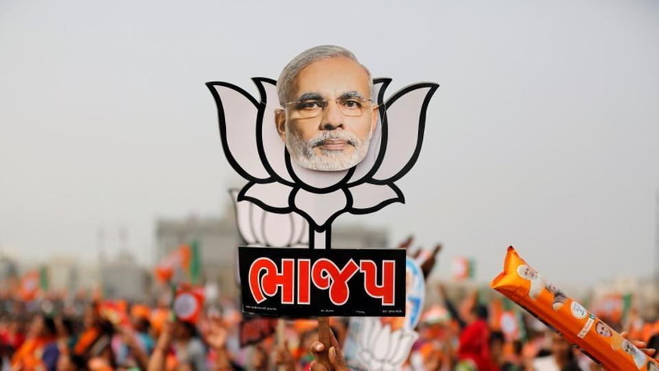 A supporter holds up a cut-out of a lotus, the election symbol of the BJP, with an image of Prime Minister Narendra Modi during a campaign meeting ahead of the Gujarat state assembly election near Ahmedabad, on December 8, 2017.