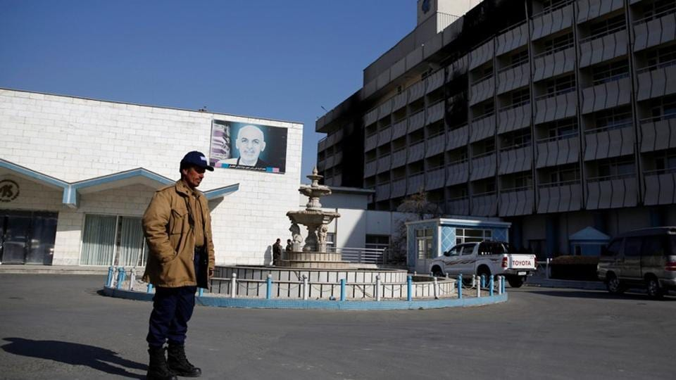 An Afghan security guard stands in front of the Intercontinental Hotel after an attack in Kabul, Afghanistan, on January 23, 2018.