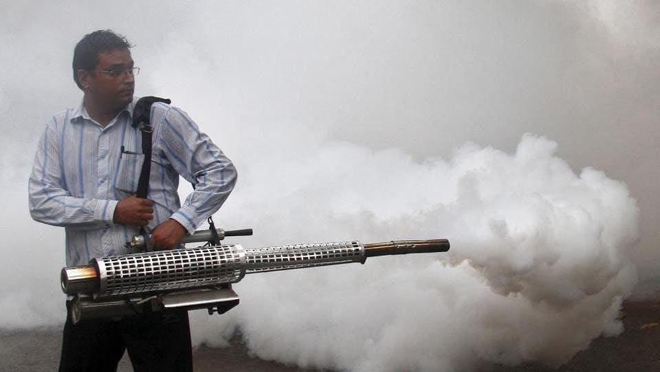 A health worker fumigates a residential area to prevent the spread of dengue fever in Chandigarh.
