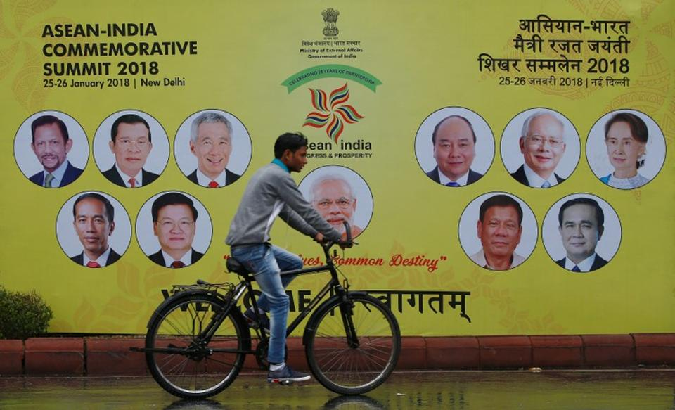 A cyclist rides past an ASEAN-India Commemorative Summit billboard the side of the road in New Delhi, India, January 23, 2018.