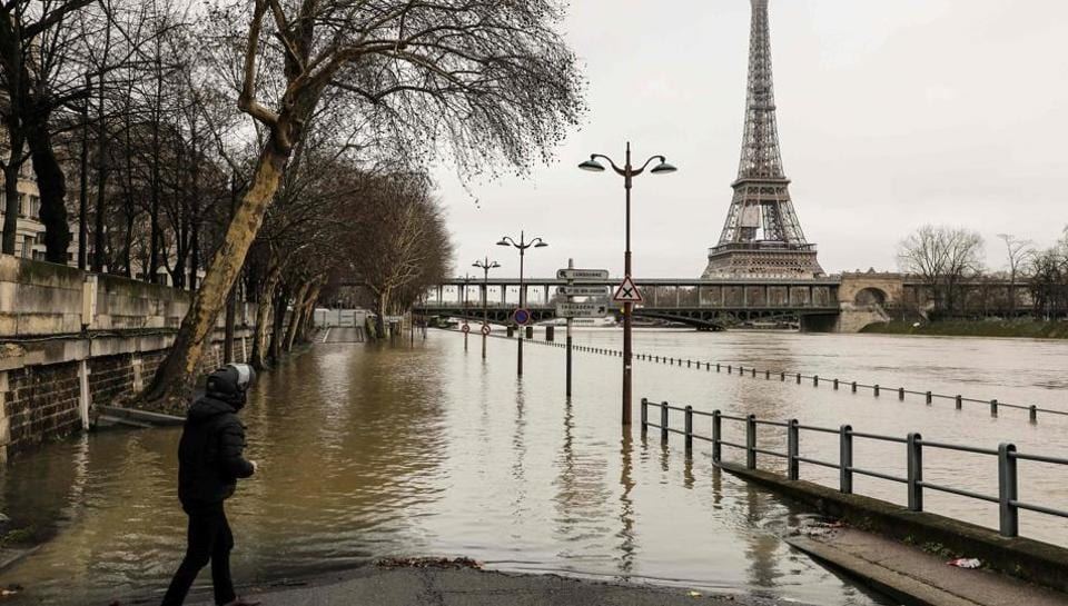 A man stands by the flooded banks of the river Seine in Paris on January 23, 2018, near the Eiffel Tower.