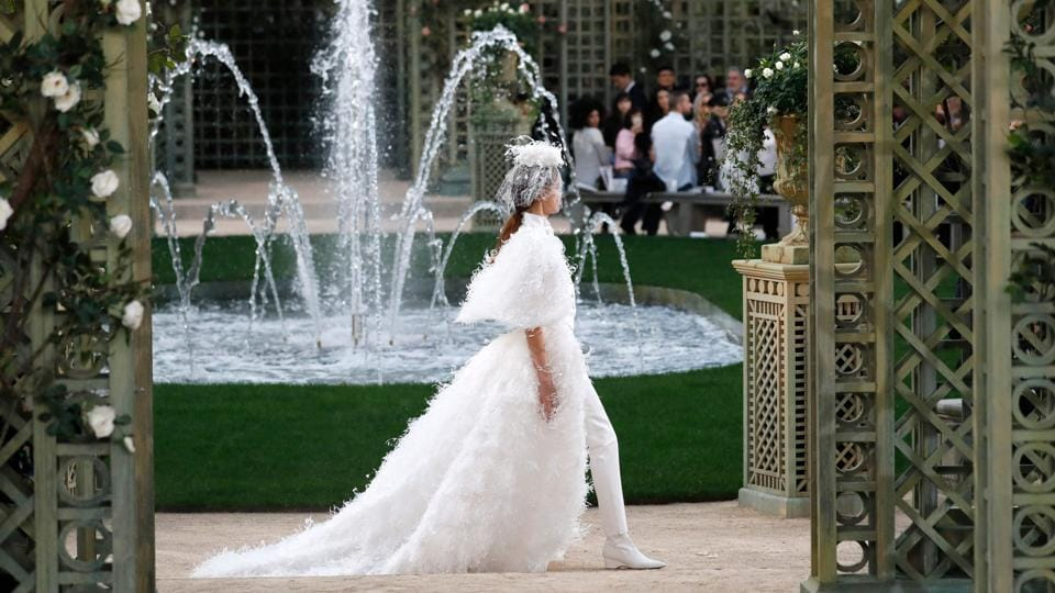 Chanel designer Karl Lagerfeld dived into the brand's archives for his pretty-in-pink haute couture Paris show Tuesday, giving its founder Coco Chanel's classics an intensely girly twist. Going back to nature, Chanel's set featured architectural wooden arbors, white roses and a water fountain. (Patrick Kovarik / AFP)