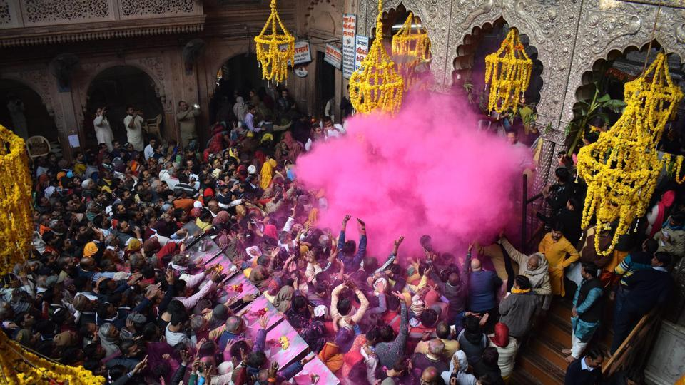 Devotees play with colours at the Banke Bihari Temple to mark the beginning of a 40-day long Holi Mahotsav in Mathura on Monday. (PTI)